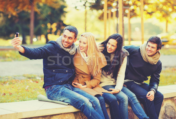 Stock photo: group of friends taking selfie in autumn park