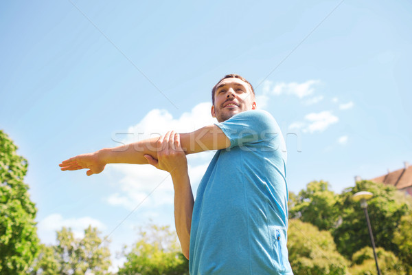ストックフォト: 笑みを浮かべて · 男 · ストレッチング · 屋外 · フィットネス · スポーツ