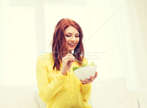 smiling young woman eating green salad at home Stock photo © dolgachov