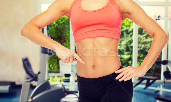 close up of woman pointing finger at her six pack Stock photo © dolgachov