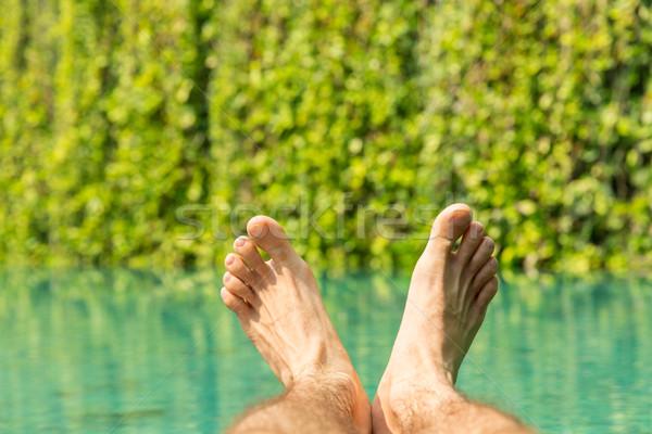 close up of male feet over resort swimming pool Stock photo © dolgachov