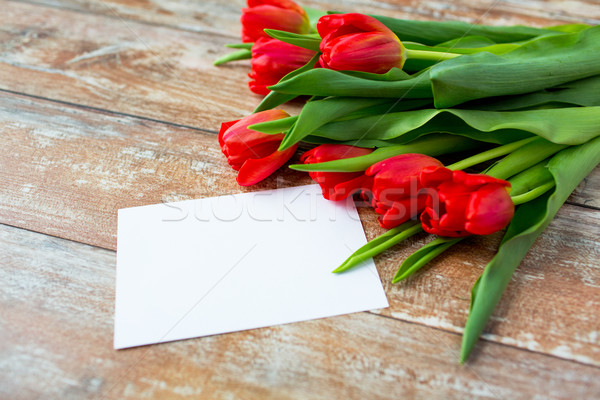 close up of red tulips and blank paper or letter Stock photo © dolgachov
