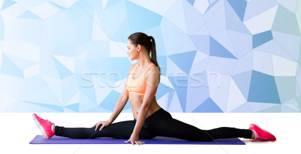 smiling woman doing splits on mat over low poly Stock photo © dolgachov