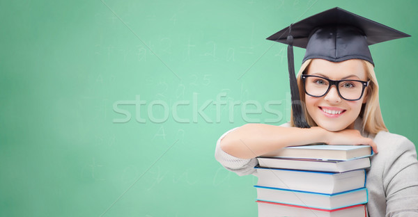 student in trencher cap with books over green Stock photo © dolgachov