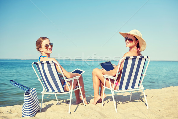 happy women with tablet pc sunbathing on beach Stock photo © dolgachov