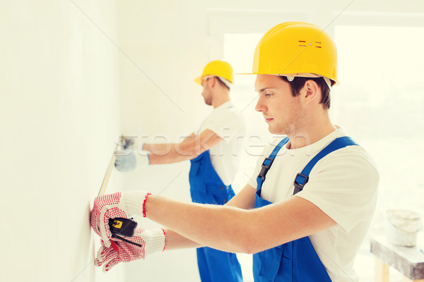 group of builders with measuring tape indoors Stock photo © dolgachov