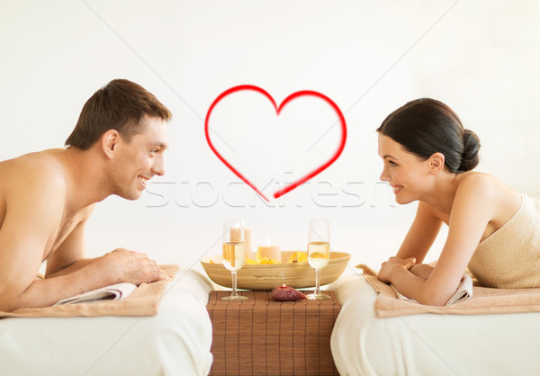 smiling couple with candles and drinks in spa Stock photo © dolgachov