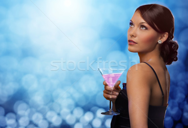 smiling woman holding cocktail over blue lights Stock photo © dolgachov