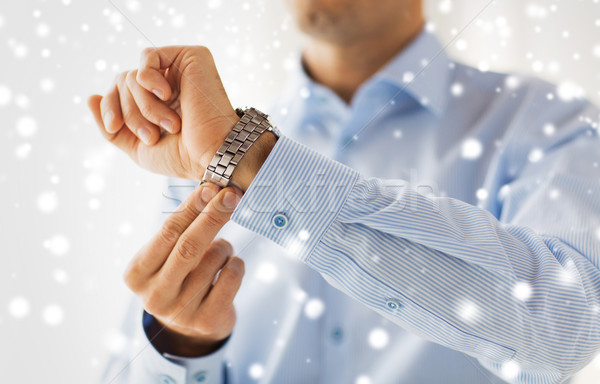 close up of man in shirt fastening wristwatch Stock photo © dolgachov