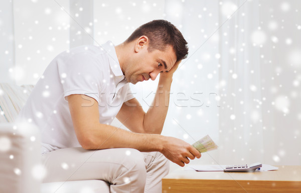 man with money and calculator at home Stock photo © dolgachov