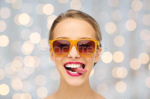 happy young woman in sunglasses showing tongue Stock photo © dolgachov