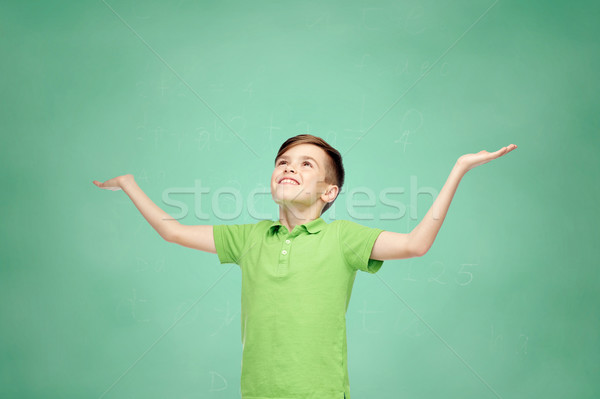 happy school boy in polo t-shirt raising hands up Stock photo © dolgachov