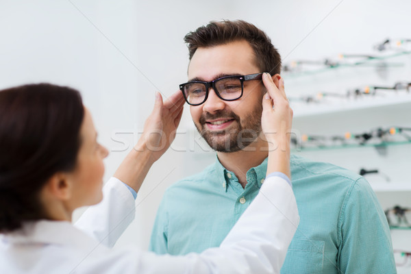optician putting on glasses to man at optics store Stock photo © dolgachov