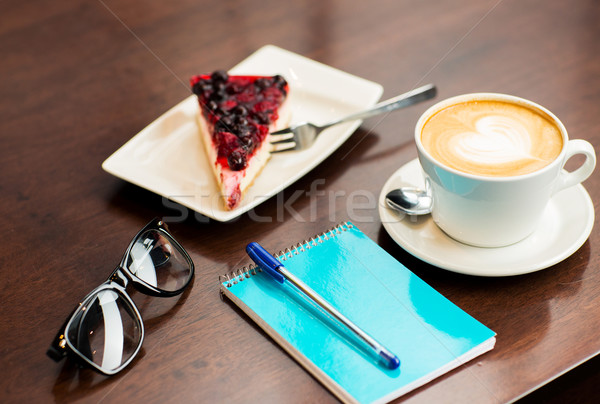 close up of notebook with pen, coffee cup and cake Stock photo © dolgachov