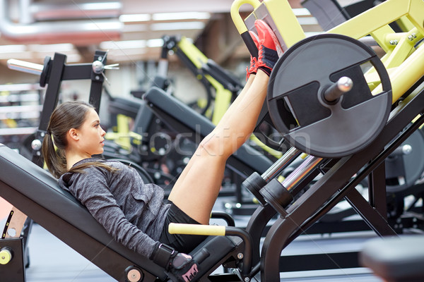 Stock photo: woman flexing muscles on leg press machine in gym