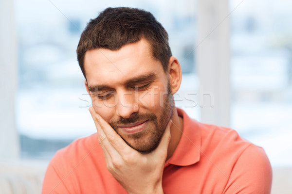 unhappy man suffering toothache at home Stock photo © dolgachov