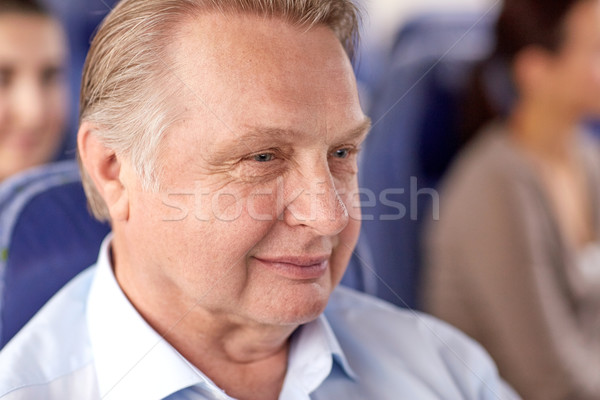 happy senior man sitting in travel bus or airplane Stock photo © dolgachov