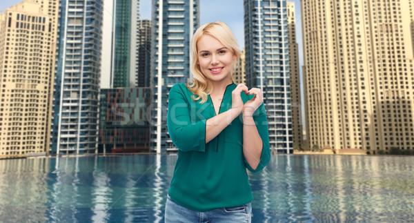 Glimlachend jonge vrouw shirt tonen hartvorm liefde Stockfoto © dolgachov