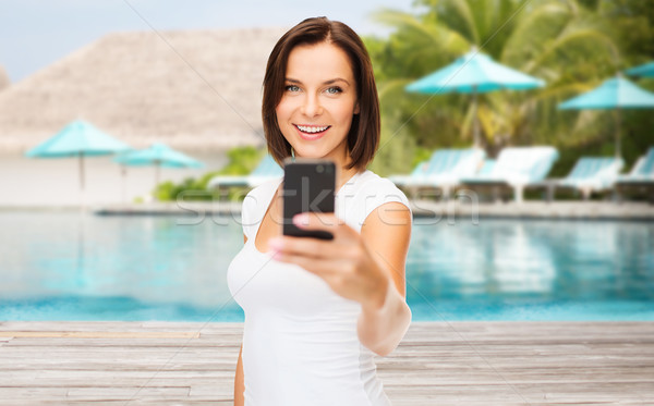 happy woman taking smartphone picture over beach Stock photo © dolgachov