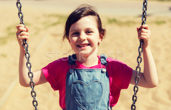 happy little girl swinging on swing at playground Stock photo © dolgachov