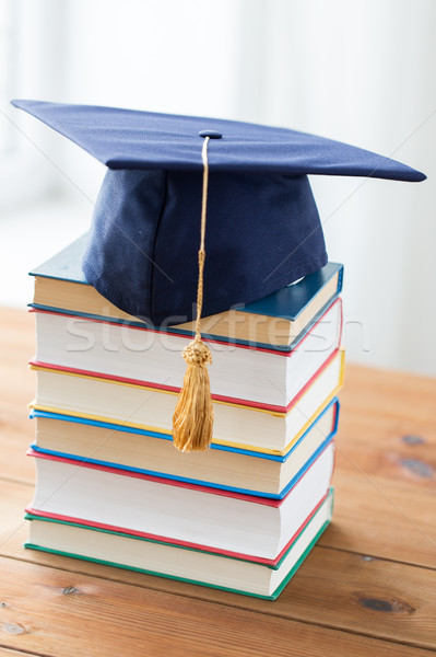 close up of books and mortarboard on wooden table Stock photo © dolgachov
