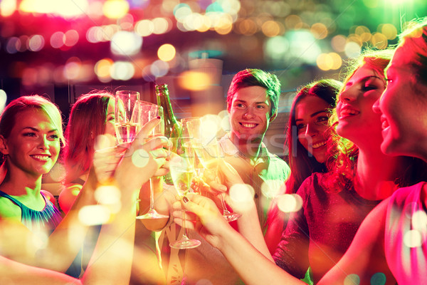 smiling friends with wine glasses and beer in club Stock photo © dolgachov
