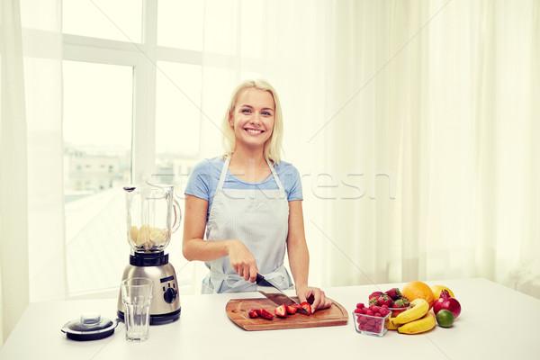 smiling woman with blender preparing shake at home Stock photo © dolgachov
