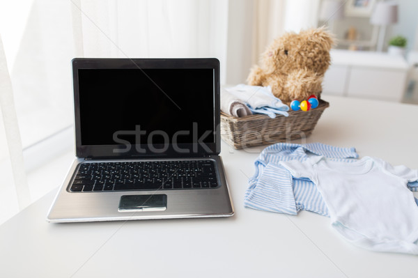 Stock photo: close up of baby clothes, toys and laptop at home