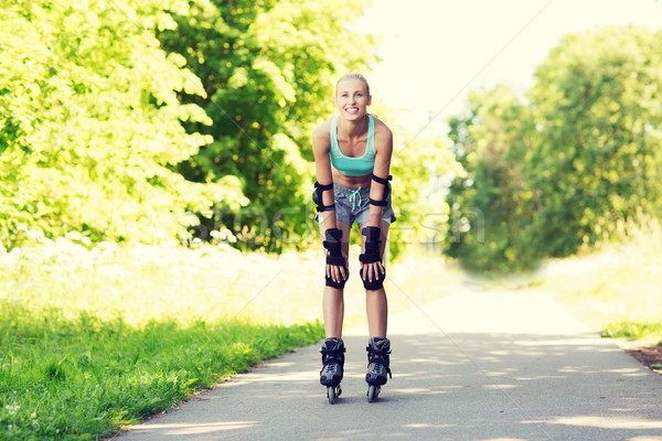 happy young woman in rollerblades riding outdoors Stock photo © dolgachov