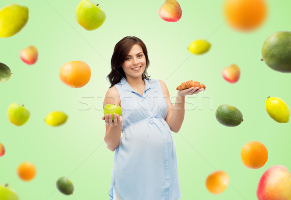 Stock photo: happy pregnant woman with apple and croissant