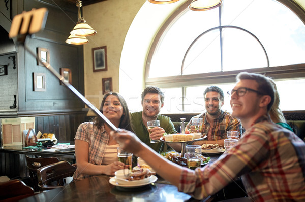 happy friends with selfie stick at bar or pub Stock photo © dolgachov