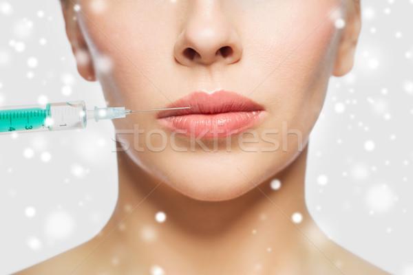close up of woman face and syringe injection Stock photo © dolgachov