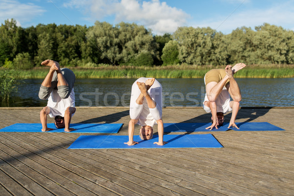 people making yoga in crane pose outdoors Stock photo © dolgachov