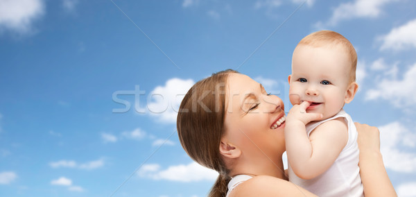 happy mother holding adorable baby over blue sky Stock photo © dolgachov