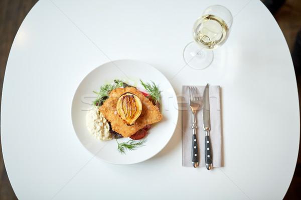 fish salad and wine glass on restaurant table Stock photo © dolgachov