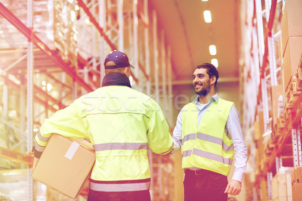 men in safety vests shaking hands at warehouse Stock photo © dolgachov
