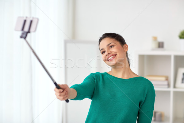 woman taking selfie by smartphone monopod at home Stock photo © dolgachov
