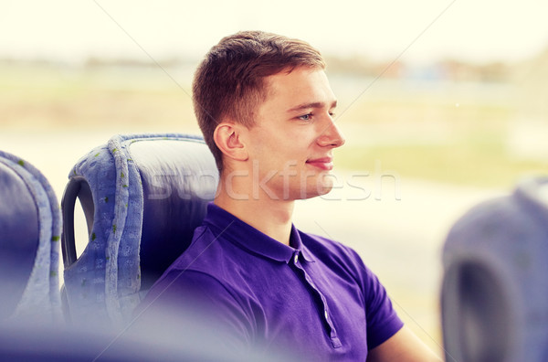 happy young man sitting in travel bus or train Stock photo © dolgachov