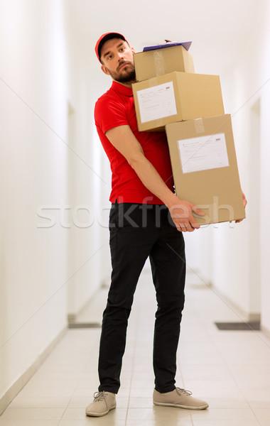 delivery man with parcel boxes in corridor Stock photo © dolgachov