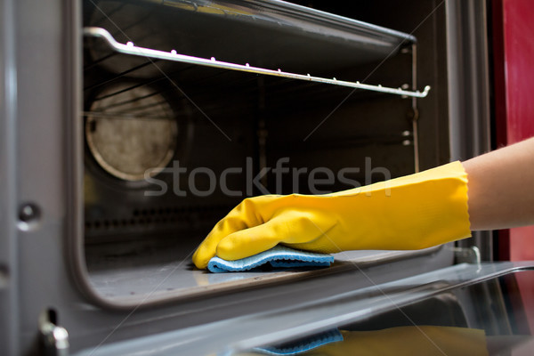 hand with rag cleaning oven at home kitchen Stock photo © dolgachov
