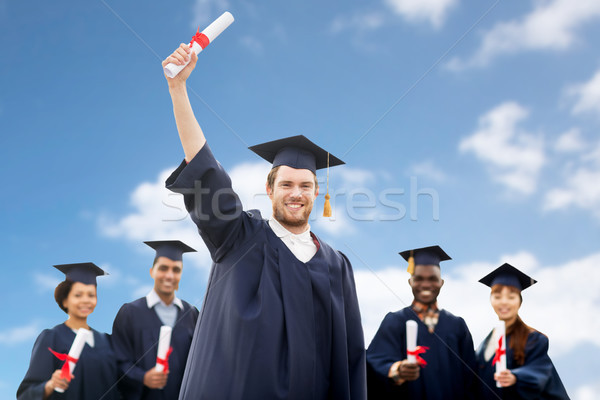 students or bachelors with diplomas over blue sky Stock photo © dolgachov