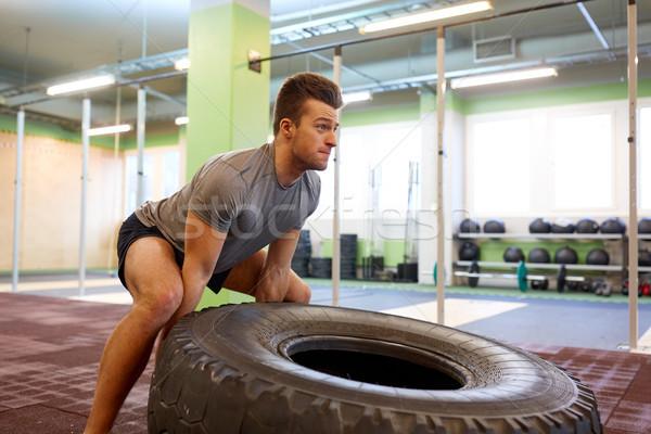 man doing strongman tire flip training in gym Stock photo © dolgachov
