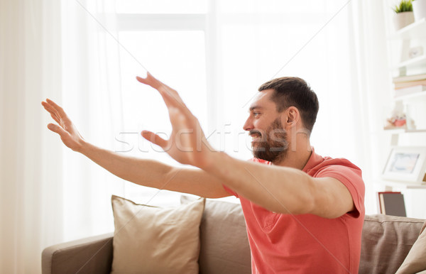 happy man touching something imaginary at home Stock photo © dolgachov