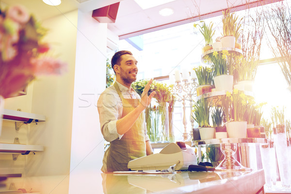 florist man or seller at flower shop counter Stock photo © dolgachov
