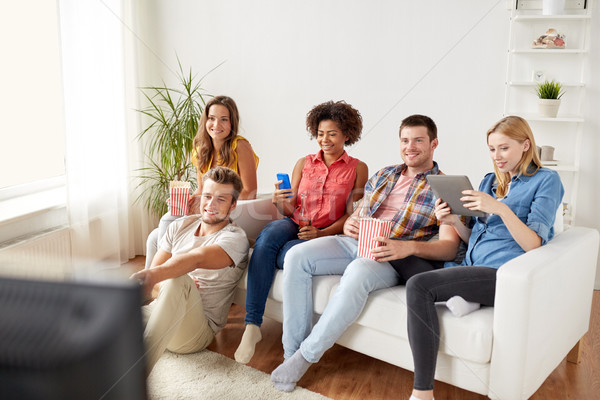 friends with gadgets and beer watching tv at home Stock photo © dolgachov