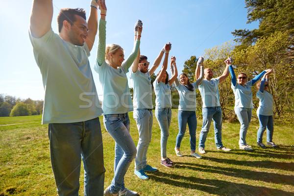 Grup mutlu el ele tutuşarak açık havada gönüllü Stok fotoğraf © dolgachov