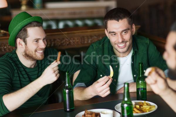 Mannelijke vrienden drinken groene bier eten Stockfoto © dolgachov