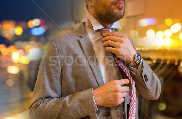 close up of man tying tie at clothing store Stock photo © dolgachov