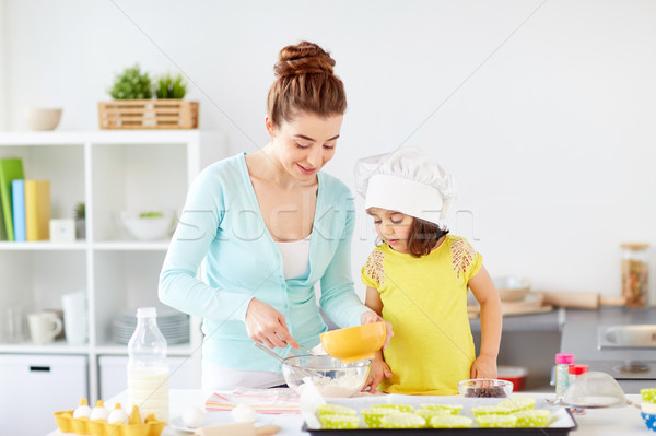 happy mother and daughter making dough at home Stock photo © dolgachov