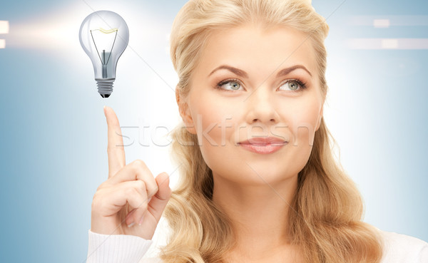 woman pointing her finger at light bulb Stock photo © dolgachov